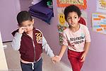 Education Preschool 3-4 year olds girl showing sympathy for sad boy, bringing him to see teacher