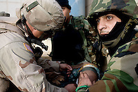 An Iraqi Minister of Interior Special Police Commando from  2nd Company, 2nd Battalion, 2nd Brigade receives medical first aid treatment   from a US ARMY trainer while an Army medic is assisting another wounded after being shot in the leg by suspected insurgents while supporting the US Army 1st batt, 506th, 101st airborne div on a battalion size operation with the purpose of drawing insurgents to the open and destroying them from static observation posts and air support in  the Mul'Hab neighborhood of Eastern Ramadi, Al Anbar Province, Iraq on Sunday Feb 11 2006. 2nd Company came under fire during the operation returning several hundred  rounds back to the insurgents that were approaching them on civilian vehicles armed with machine guns. one hour in the operation an Iraqi senior non commissioned officer fired accidentally (  tech therm: negligent discharge) his AK 47 automatic rifle almost wounding several comrades and US military trainers that where operating next to him. the unit continued the mission making several tactical mistakes that opened the way for a suspected insurgent vehicle to approach from  close distance and fire accurately on the unit that was on an open street without cover. Two Commandos suffered injuries and were evacuated by the US Army Medivac system. A third received two rounds in his back armor plate but suffered no injuries. The operation lasted several more hours but after the accident the Commandos relaxed even further providing  very ineffective security.   The insurgency operates extensively in the Mul'Hab neighborhood attacking the coalition  and  Iraqi forces on a regular  bases.