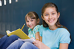 USA, Illinois, Metamora, Portrait of two girls (8-9) sitting at lockers in school corridor and doing homework