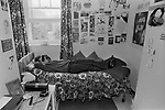 Woman in prison cell UK 1980s. Female prisoner lying on bed with her possessions, photographs and drawing stuck to the wall of her cell as decoration. HM Prison Styal Wilmslow Cheshire England 1986