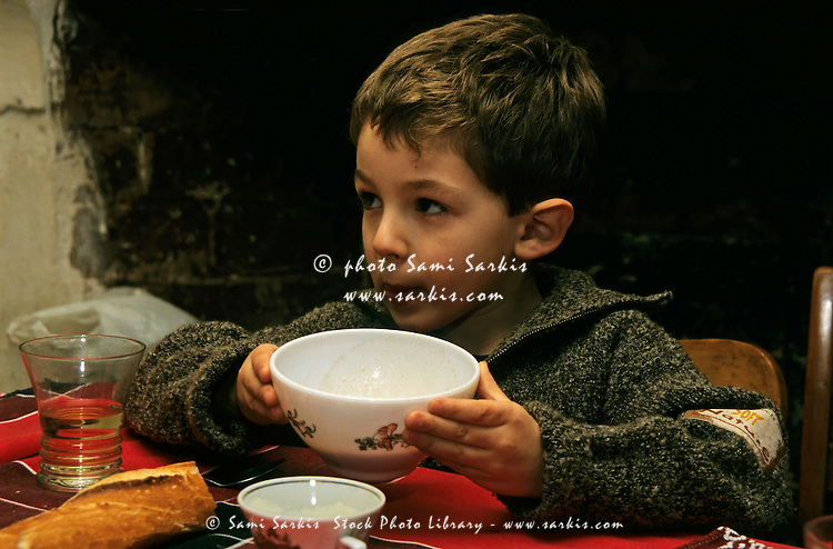 Young boy eating soup for lunch at the table.