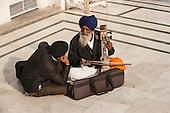Amritsar, Punjab, India. The Golden Temple - Harmandir Sahib. Two Sikh musicians sitting cross-legged on the marble floor, one playing a Sarangi using a bow.