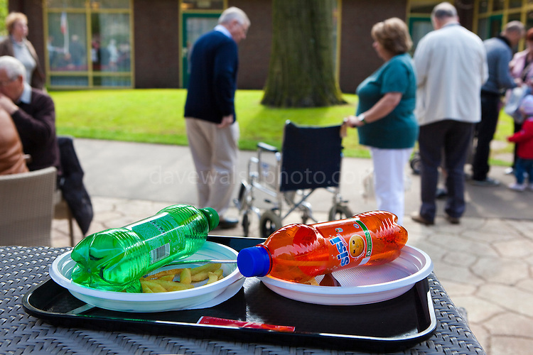 Couple leaving their junk food tray and leaving with their wheelchair at the Keukenhof tulip and flower show in Lisse, Holland - Netherlands Editorial Use only.