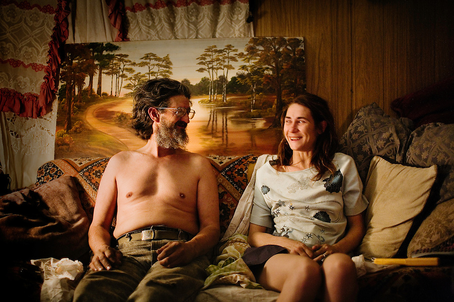 """Niland, Calif., March 28, 2008 - Tumbleweed (his only name given) sits on the couch with his best friend's wife, Moria Morofsky, in the Morofsky's trailer. Weeds, as he likes to be called by his friends, visits the couple daily to watch movies and smoke pot. He says of Moria, """"If Ben had not married her, I surely would have."""" ."""