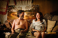 "Niland, Calif., March 28, 2008 - Tumbleweed (his only name given) sits on the couch with his best friend's wife, Moria Morofsky, in the Morofsky's trailer. Weeds, as he likes to be called by his friends, visits the couple daily to watch movies and smoke pot. He says of Moria, ""If Ben had not married her, I surely would have."" ."
