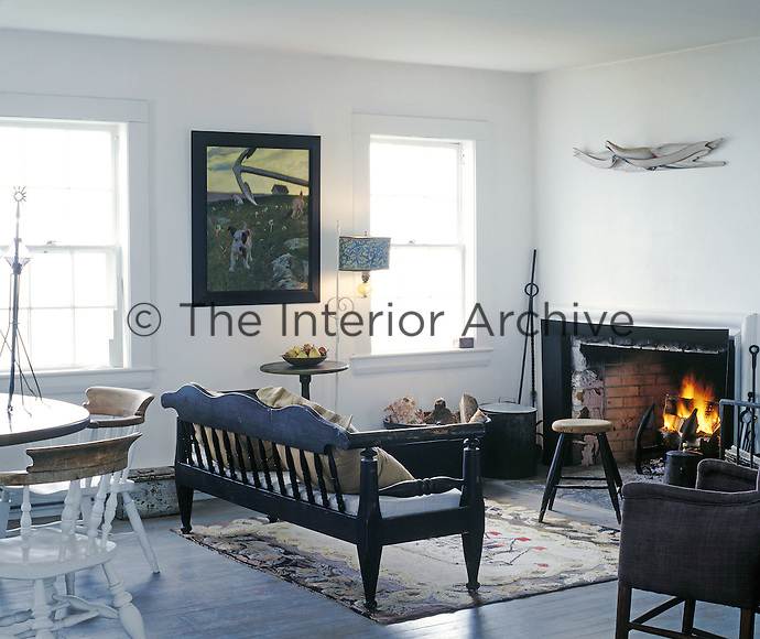 A cheerful fire casts a warm glow around this simply furnished living/dining room