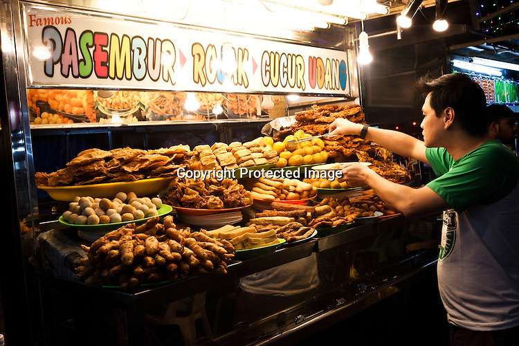 A local takes a plate of fried rojak at a Chinese Hawker stall in Gurney Drive, Georgetown in Penang, Malaysia. Photo: Sanjit Das/Panos