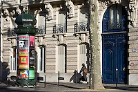 Woman walks past obelisk advertising theatre productions in Parisian street, Boulevard St Germain, Latin Quarter, France
