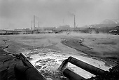 Norilsk, Russia  .May-June 1997.The nickel factory in Norilsk dumps factory chemical water into a controlled pool. It constantly steams with chemicals and is completely accessible to anyone passing by, even children..