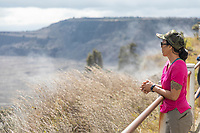 A woman looks at Halema'uma'u Crater and steam vents at Hawai'i Volcanoes National Park, Big Island.