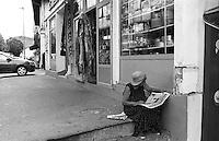 Belgrado, una donna legge il giornale seduta su dei gradini in strada --- Belgrade, a woman reads the newspaper while sitting on the steps in the street