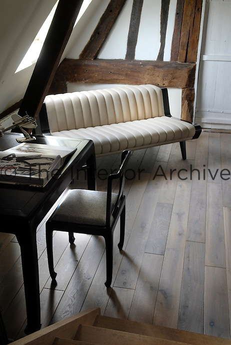 In a corner of the office a 1940s beige leather sofa sits in perfect harmony with the medieval half-timbering