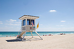 Lifeguard hut stands sentinel over swimmers and sun worshippers.