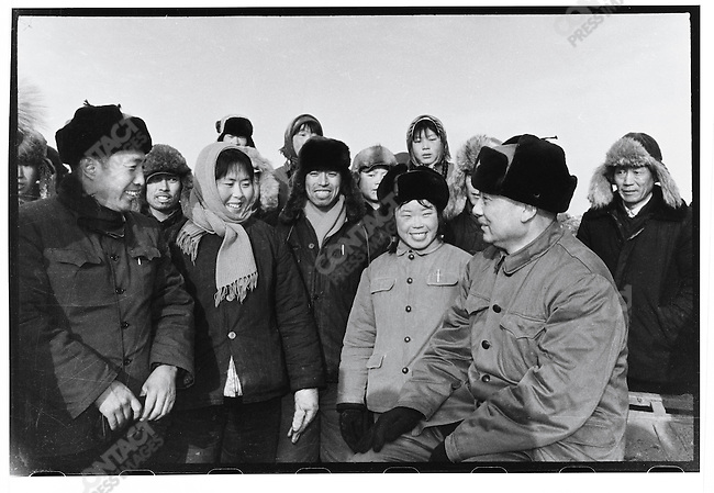 """Part one of two picture montage was published in the Heilongjiang Daily in December 1974 as part of a photo essay devoted to an irrigation project in Shuangcheng County. The site was officially inspected by Liu Guangtao (center, with star on hat), first secretary of the Provincial Party Committee and director of the Provincial Revolutionary Committee, and his deputy Yang Yichen (to his left). Li Zhensheng was not able to include in a single frame the two dignitaries greeting local Party leaders. The editors asked him to make one image from two prints by cutting and pasting them together. Moving scissors around and additional retouching made the scene seem more """"real"""" and upbeat."""