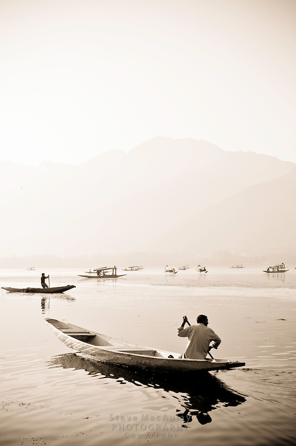 Toned black and white photograph of traditional Kashmiri shikaras, or gondolas, Dal Lake, Srinagar, Kashmir, india..