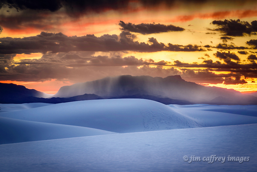 The dune field at White Sands National Monument at twilight as rain falls on the distant San Andreas Mountains