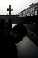 "A man looks at a reflecting pool on the grounds of the Memorial Hall of the Nanjing Massacre in Nanjing, China, on Thursday, Dec. 13, 2007. After two years of renovations, the Memorial Hall of the Nanjing Massacre reopened to the public on Dec. 13, 2007, the 70th anniversary of the 6-week massacre by Japanese troops that started Dec. 13, 1937 and claimed more than 300,000 lives.  The commemoration comes amid renewed controversy about the accuracy of historical accounts of the massacre.  The massacre is also known as ""The Rape of Nanking."""