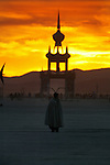 A woman enjoys the morning sunrise looking towards the Temple of Honor at Black Rock Desert - High Rock Canyon during the Burning Man Festival. .