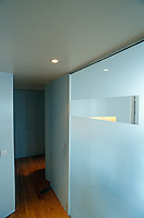 The living area is compartmentalised by a series of opaque glass walls
