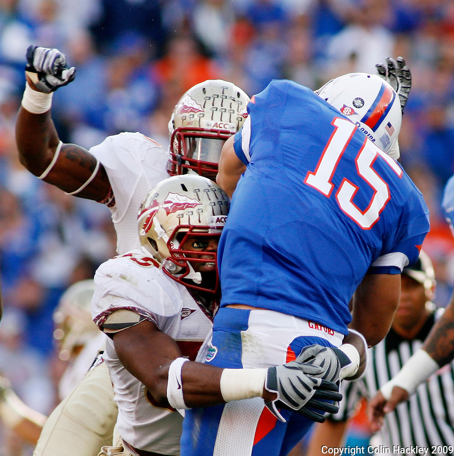 GAINESVILLE, FL 11/28/09-FSU-UF FB09 CH02-Florida State's Dekoda Watson, below, grabs Florida's Tim Tebow as Seminole Nigel Bradham closes during first half action Saturday at Florida Field in Gainesville. .COLIN HACKLEY PHOTO