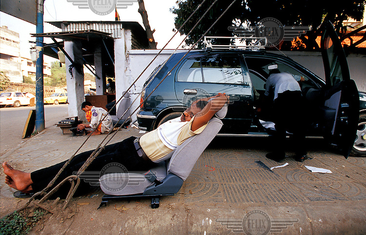 Bangladesh; Dhaka.  A mechanic sleeps in the removed driver's seat of a car his colleague is cleaning on the pavement in the centre of Dhaka.