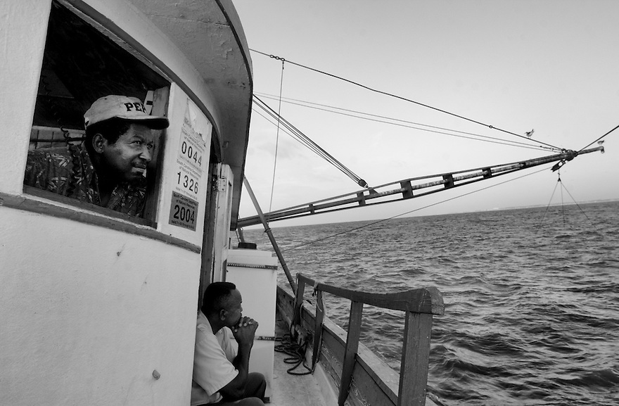 Shrimpers Eugene Orage and Diogenese Miller enjoy the morning as they make their first drag of the day. Reduced access to waterways, strict regulations and increasing seafood imports are spoiling domestic shrimping — a traditional Gullah Geechee vocation.