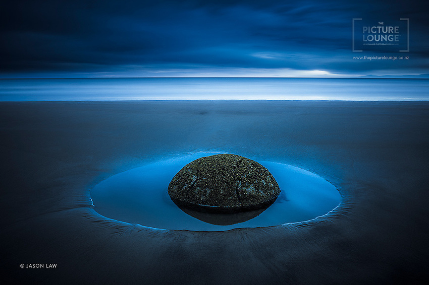 An award-winning image of a solitary Moeraki boulder at rest in its tidal puddle by Queenstown based landscape photographer Jason Law.