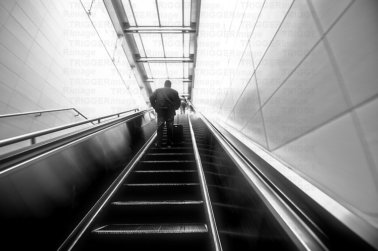 Urban environment with silhouetted man in high contrast going up a steep escalator
