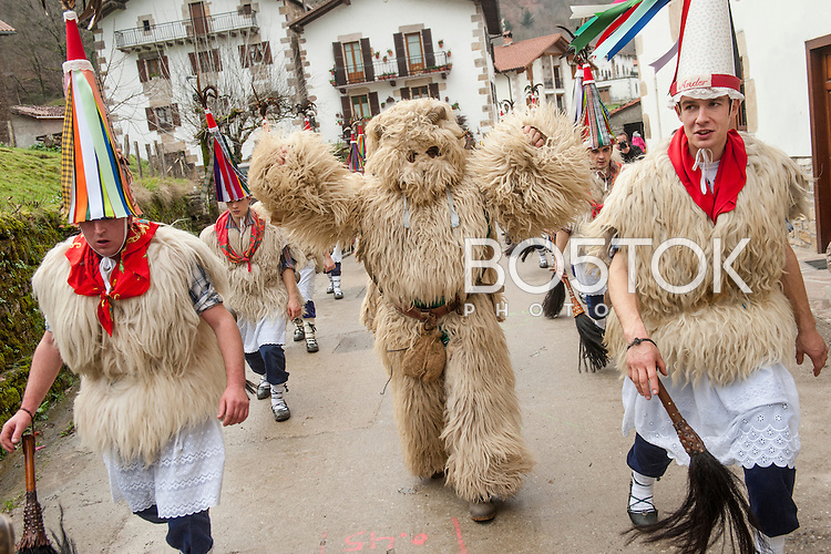 "A man dressed up as a bear, performs among people dressed up in ""Joaldunak"" (""those who play the bell"") costume, during the celebration of an ancient traditional carnival. Ituren (Basque Country). February 1, 2016. The ""Joaldunak"" (""those who play the bell"") is a character that takes part in the carnival at the villages of Ituren and Zubieta carrying sheep furs and big cowbells tied to their backs to wake up the earth, looking for a good new year, a good harvest and to keep away the bad spirits.  (Gari Garaialde / BostokPhoto)"