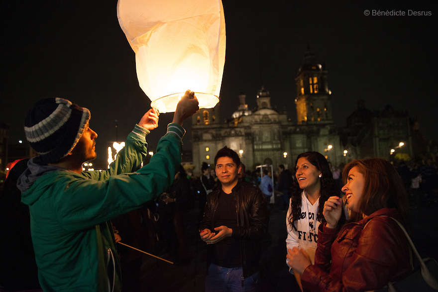 Demonstrators light a candle during a massive march in support of the 43 missing Ayotzinapa's students, on a day normally reserved for the celebration of Mexico's 1910-17 Revolution, in Mexico City, Mexico on November 20, 2014. Parents of the 43 missing students still do not believe the official line that the young men are all dead. Criticism of the government has intensified in Mexico and the country has been convulsed by protests. Many are demanding justice and that the search for the 43 missing students continue until there is concrete evidence to the contrary. Mexico officially lists more than 20 thousand people as having gone missing since the start of the country's drug war in 2006, and the search for the missing students has turned up other, unrelated mass graves. (Photo by Bénédicte Desrus)