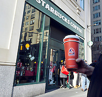 A Teavana customer outside a Starbucks in the Upper East Side neighborhood of New York seen on Friday, November 16, 2012. The coffee giant Starbucks is reported to be buying the Atlanta-based chain of tea stores for $620 million in cash.  (© Richard B. Levine)