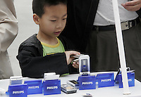 A kid looks at Philips mobile phones at a street-side display in Shanghai, China..