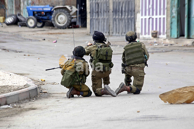 Israeli soldiers take position during clashes with Palestinian protesters in the village of Beit Ummar near the southern West Bank city of Hebron on October 8, 2015. There have been at least eight stabbing attacks since the beginning of the month, when a Palestinian killed two Israelis in Jerusalem's Old City, helping to prompt a security crackdown and spread riots. Photo by Muhesen Amren