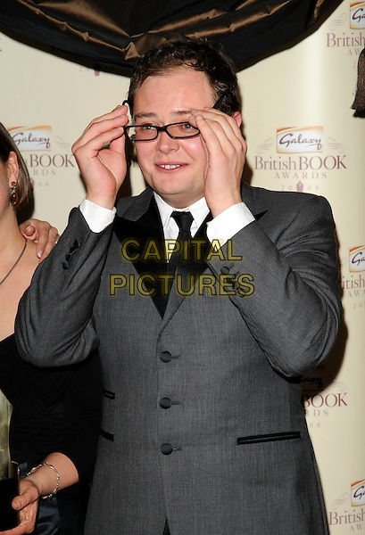 ALAN CARR .Attending the Galaxy British Book Awards held at the Grosvenor Hotel, Park Lane, London, England,.April 9th 2008..half length holding putting on glasses funny grey suit jacket gray .CAP/CAN.©Can Nguyen/Capital Pictures