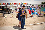 Freddy Warneke, right, brother of William Warneke, one of the 19 Granite Mountain Hotshots who perished in the Yarnell Fire, comforts his widow, Roxanne Warneke, at a makeshift memorial outside Fire Station 7 in Prescott, Arizona, July 2, 2013.
