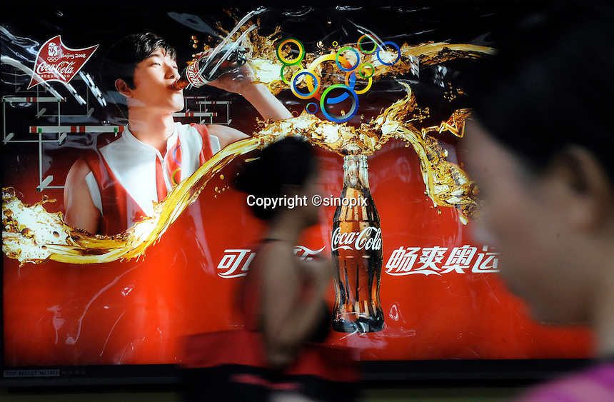 A Coca-cola advert featuring Chinese 110 meters hurdler Liu Xiang (left) on an advertising hoarding outside Chaoyang Park, where the beach volley is being played. After years of hype and multi-million dollar endorsements Liu Xiang disappointed the whole of China and failed before the first hurdle and is out of the games with injury..