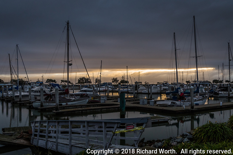 A break in the weather, on the horizon behind the tall naked masts of sailboars moored at the San Leandro Marina.  In the foreground a red DANGER sign hangs over yellow caution tape.