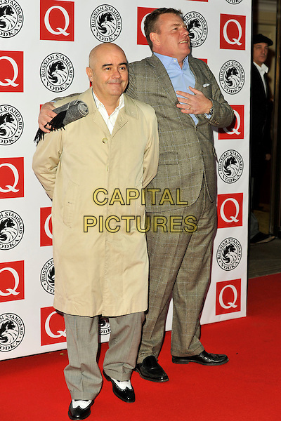 MADNESS - Chris Foreman & Suggs.The Q Awards 2010 at The Grosvenor House Hotel, London, England. .October 25th, 2010.full length beige grey gray blue shirt suit hand arm side profile trench coat on chest.CAP/MAR.© Martin Harris/Capital Pictures.