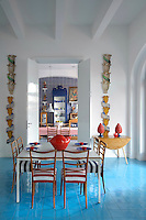 Striped loose covers on the 1950s chairs in the dining room are echoed by the checked wall tiles in the kitchen beyond