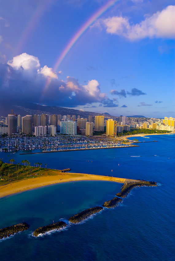 Aerial view of the Ala Wai Yacht Harbor (with Magic Island in foreground) with Waikiki behind and a rainbow overhead, Honolulu, Oahu, Hawaii, USA