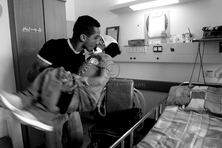 Hamdi Aman, takes care of his daughter Maryia in Alin, a rehabilitation hospital in Jerusalem, October 11, 2007. Maryia, who was paralyzed from the neck down after an Israeli attack on militants in Gaza in May 2006 lost her mother, grandmother, uncle and older brother in the attack. Maryia was taken to Alyn rehabilitation hospital in Jerusalem. The Israeli Defense Ministry covered her medical expenses and sponsored her father and younger brother to live with her at the hospital. Hamdi has 50 seconds to connect and disconnect Maryia from the respirator to move her from the wheelchair to the bed.