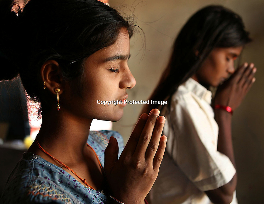 Akshata Jivoji (left) and Malashri Kamble perform their morning prayers in their hostel room at Vimochana Sangha's school for the children of Devadasis in Malabad, India.  The Devadasi system is an ancient system of religiously-sanctioned prostitution.  Because the belief is that all female children of Devadasis should themselves become Devadasis, the school was created to remove the children from the culture in which this practice took place and instead offer them an education.  All students receive free tuition, books, uniforms, food and medical care. Graduates have gone on to become teachers, nurses, engineers etc.