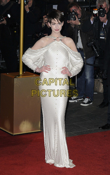 Anne Hathaway (wearing Givenchy).World Premiere of 'Les Miserables' at the Odeon & Empire cinemas Leicester Square, London, England..December 5th 2012.full length white dress gown bejewelled sleeves satin silk draped beads beaded hands on hips batwing off the shoulder .CAP/CAN.©Can Nguyen/Capital Pictures.