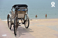 Parked Rickshaw with drivers bathing in ocean (Licence this image exclusively with Getty: http://www.gettyimages.com/detail/83154225 )