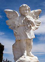 Angel Statue at the Chilili Cemetary in New Mexico. The dozens of tombstones and memorial plaques have been created entirely of large sheets of tin, mounted on marble with the lettering out with a nail by Horace McAfee,