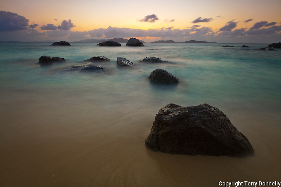 Virgin Gorda, British Virgin Islands, Caribbean<br /> Boulders awash in the surf of Little Trunk Bay near the Baths. Sunset afterglow over Tortola across Sir Francis Drake Channel.