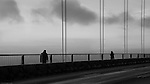 Two silhouetted people walking toward each other on a bridge in the clouds.