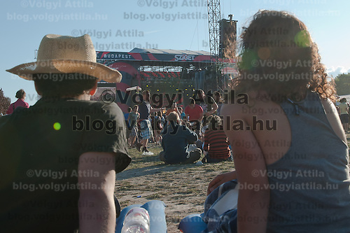 A coupple sits in front of the main stage during a concert on Sziget festival held in Budapest, Hungary on August 10, 2011. ATTILA VOLGYI