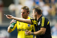 Chris Birchall (8) of the Columbus Crew talks with head coach Robert Warzycha. The Columbus Crew defeated the Philadelphia Union 2-1 during a Major League Soccer (MLS) match at PPL Park in Chester, PA, on August 29, 2012.