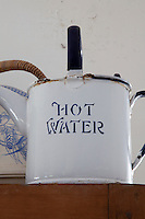 An old enamel kettle labelled 'hot water' on display in the kitchen
